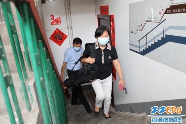 郑州市第三十一高级中学校长贾惠芬等领导带着书包等慰问品到学生家中慰问