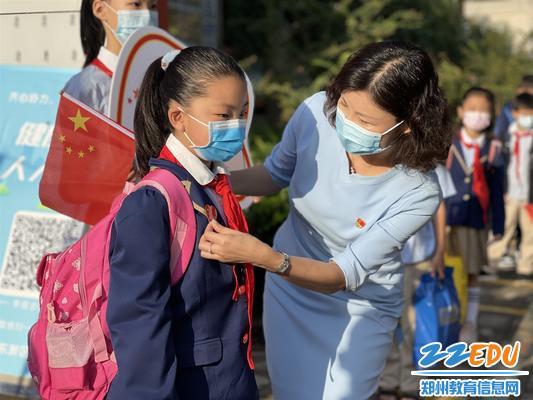 郑东新区蒲公英小学校长蔡瑞敏为学生张贴国旗胸贴