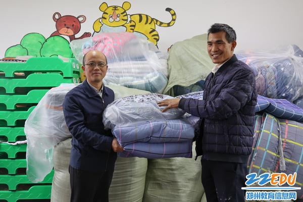 2.郑州市信息技术学校副校长王宏亮为二郎庙小学赠送住宿用品