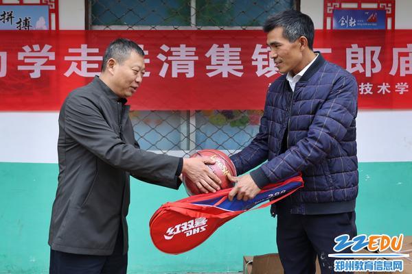3.郑州市信息技术学校副校长张继波为二郎庙小学赠送体育器材