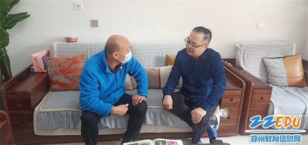 2学校党总支书记董国成和离(退)休教师赵鹏交谈