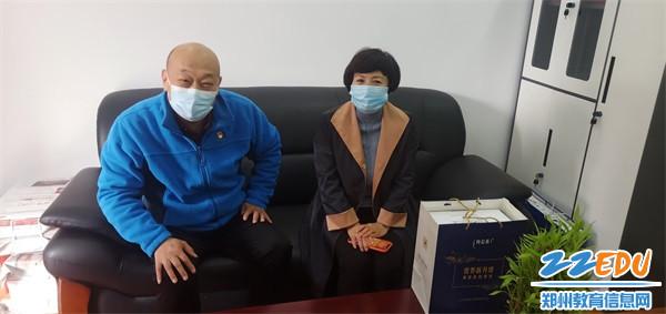 3学校党总支书记董国成和离(退)休教师李金慧交谈
