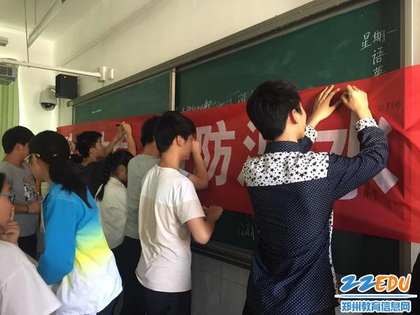 """学生们在""""珍爱生命 预防溺水""""宣传条幅上签名"""
