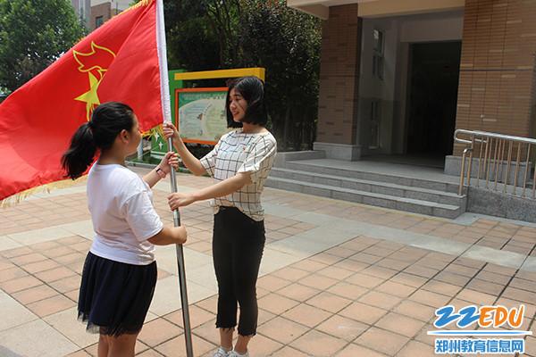 党员教师熊灿向大队干部传递队旗