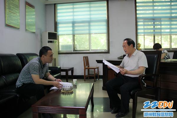 学校办公室主任张磊与村支书商讨帮扶措施