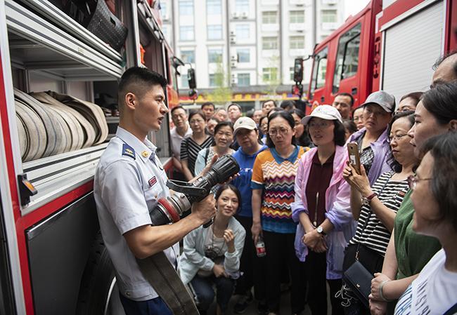消防战士向学员讲解消防车上的消防设备如何使用