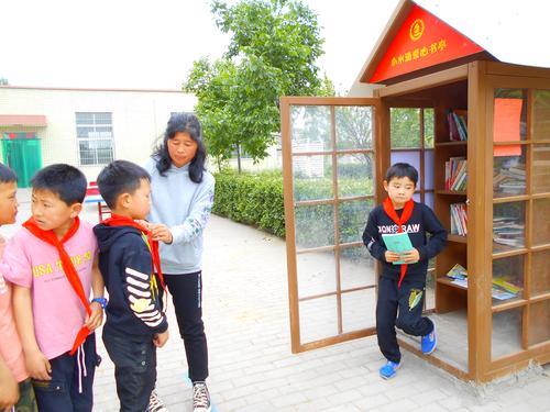 新郑新村水泉小学毛林英在为学生整理红领巾