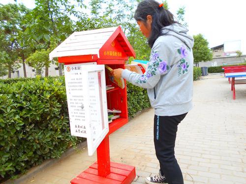 新郑新村水泉小学毛林英在整理校园书橱