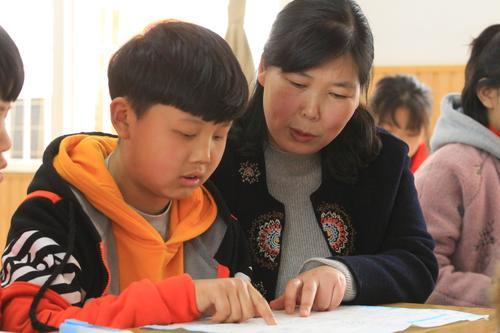 郑州市管城回族区腾飞路七里河小学张敏鹏在课堂上辅导学生