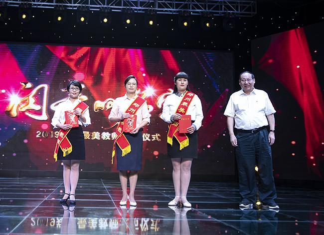 郑州市教育局党组成员、副局长张大龙为2019年郑州最美教师颁奖。