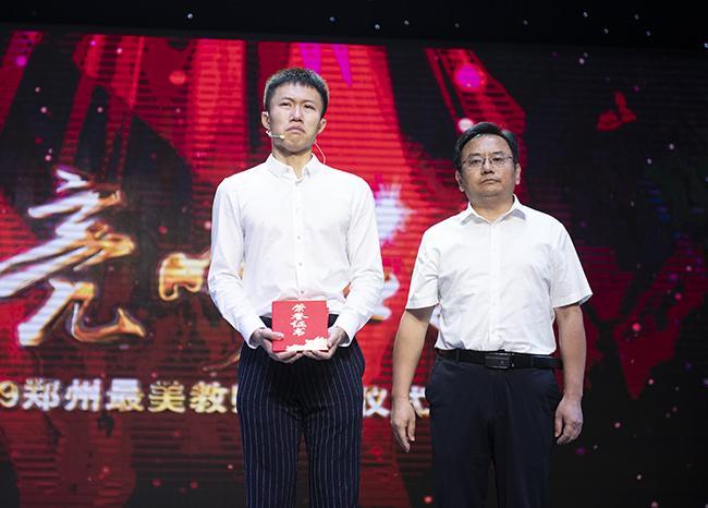 郑州市教育局副局长葛飞为2019年郑州最美教师周超颁奖,周超家属上台领奖并合影留念。