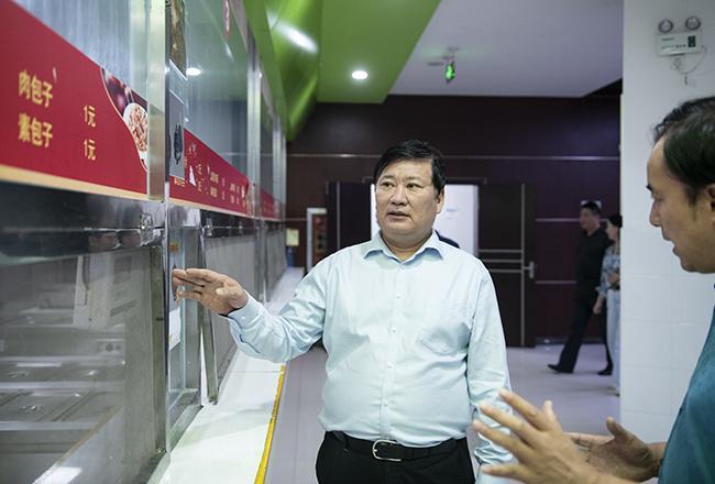 郑州市教育局党组书记、局长王中立一行在管城回族区外国语学校视察午餐供餐情况1。