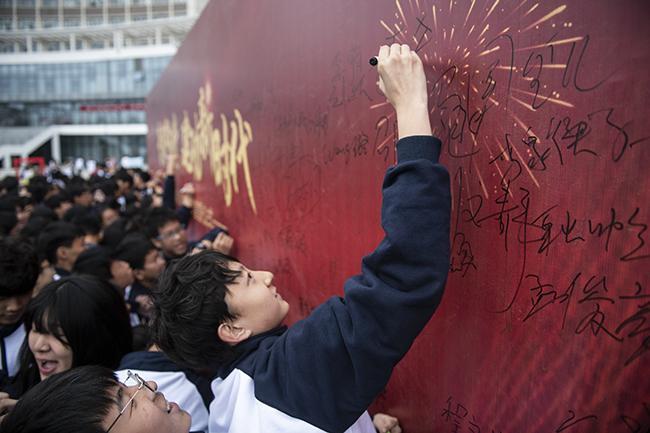 学生在签名墙上签名