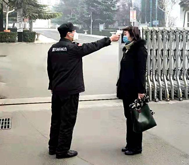 保安师傅对入校工作人员测量体温