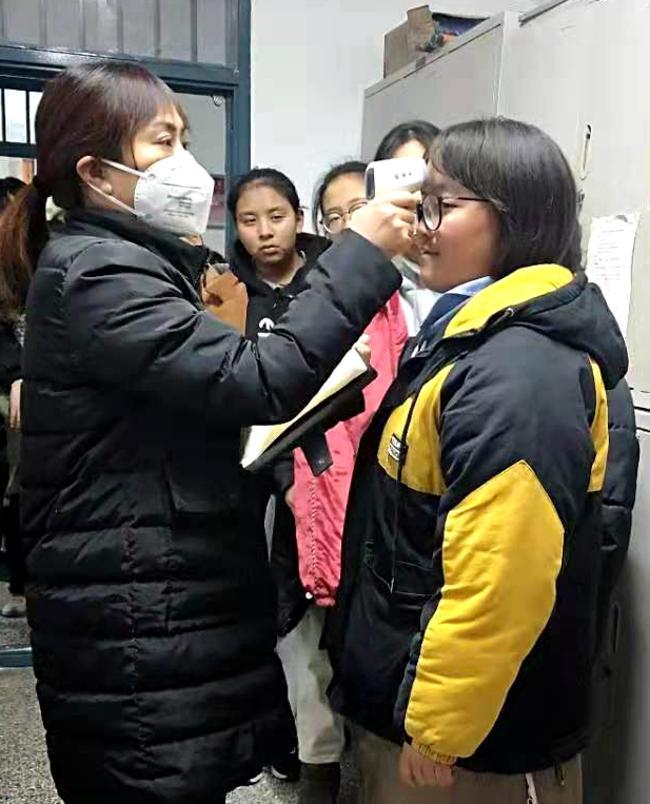 宿管老师给学生测量体温