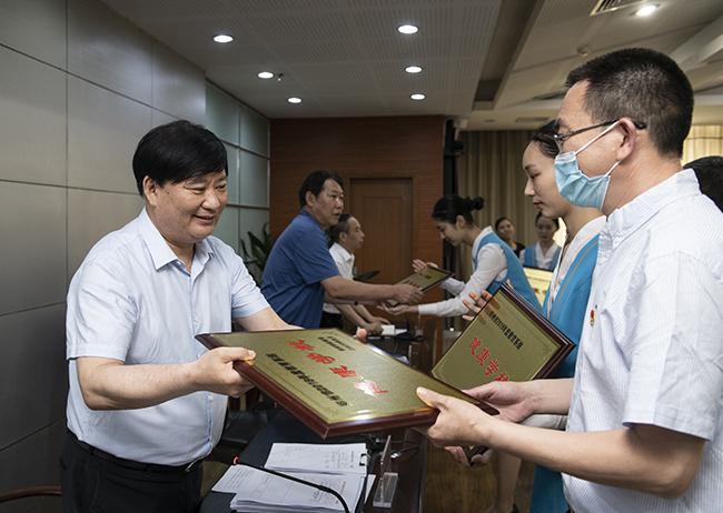 """参会领导为获得""""2019年郑州市无烟单位、健康单位暨郑州市教育系统健康学校""""荣誉称号的单位代表授牌。"""